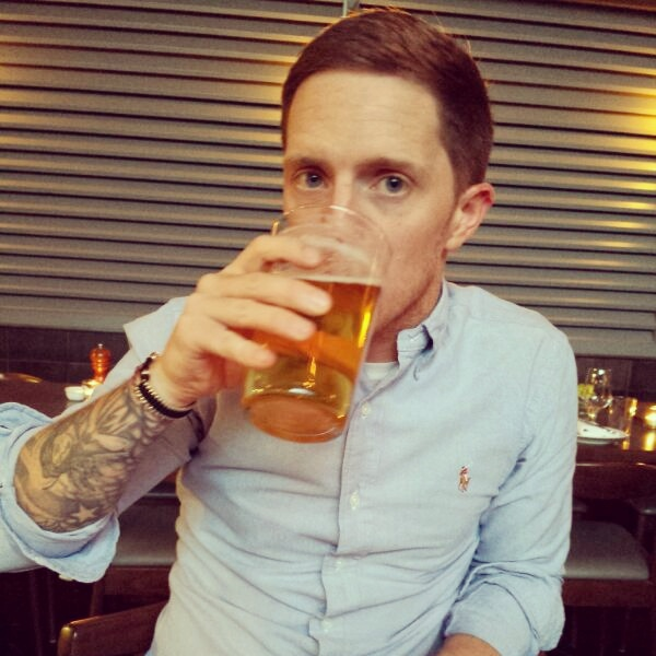 man-in-blue-shirt-drinking-pint