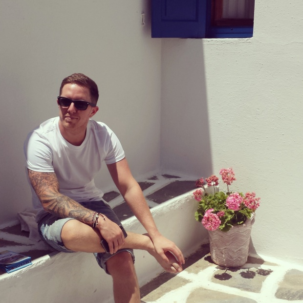 man-sat-on-ledge-next-to-plant-pot-in-mykonos